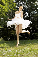 Young happy woman in white dress jumping in midair with bubbles outdoors