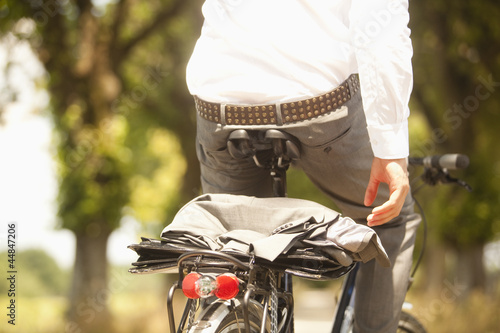 Close-up of coat and briefcase on back of young businessman's bicycle