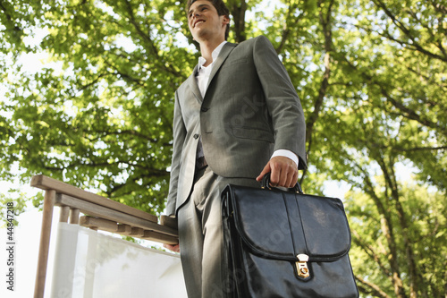 Low angle view of young businessman walking and carrying briefcase and chair