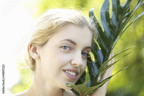 Portrait of young woman posing with leaf outdoors