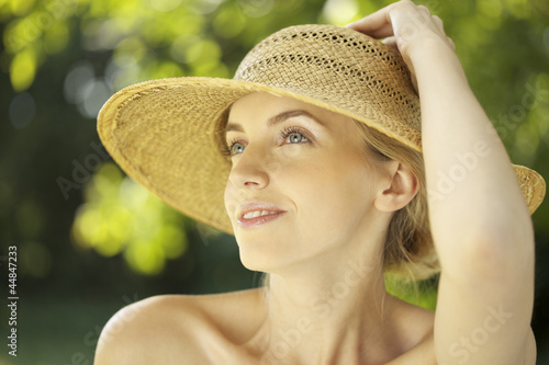 Portrait of young woman in straw hat outdoors
