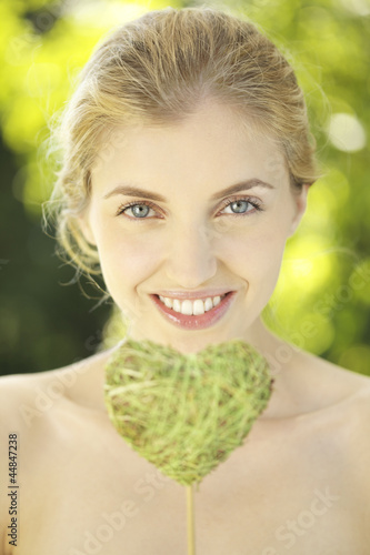 Portrait of young woman holding heart shape leaf on a stick