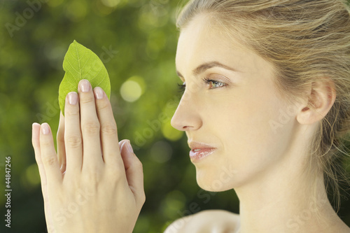 Portrait of young woman holding a leaf outdoors