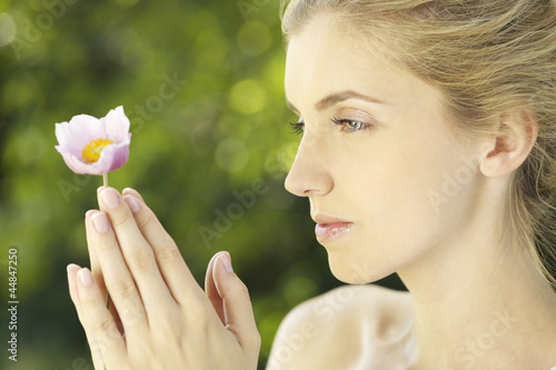 Portrait of young woman holding a flower outdoors