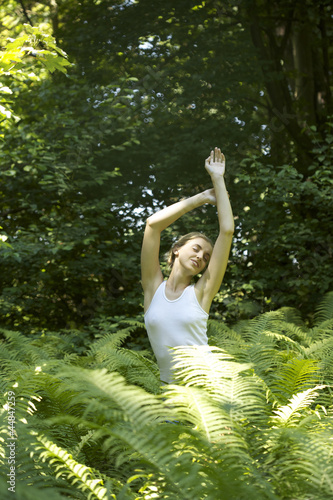 Portrait of young woman stretching among fern leaves outdoors
