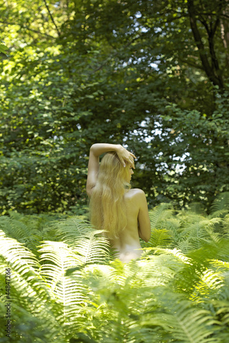 Rear view of young nude woman standing among fern leaves outdoors