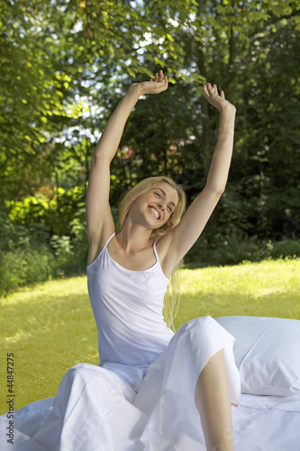 Portrait of young woman in bed outdoors stretching