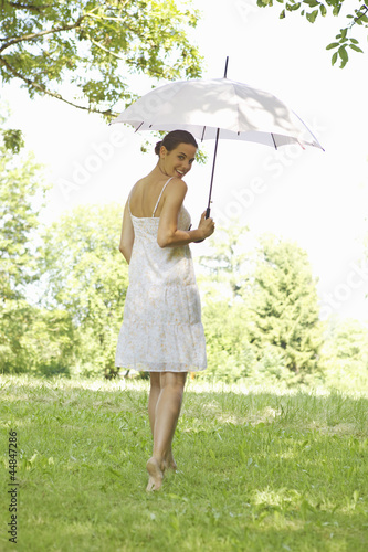 Portrait of young woman walking in grass holding an umbrella