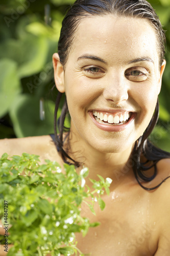 Portrait of young woman with wet hair holding plant outdoors