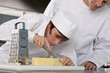 Chef watching trainee slice cheese in commercial kitchen