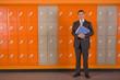 Teacher holding paperwork standing near school lockers
