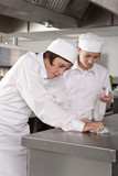 Trainee chefs cleaning work surface in commercial kitchen