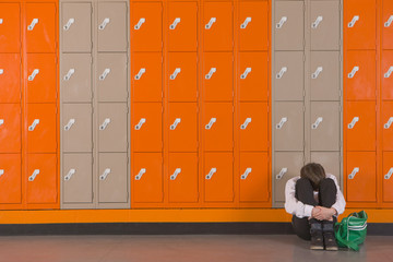 Unhappy student sitting on floor near school lockers