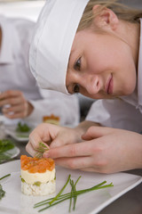 Trainee garnishing food in commercial kitchen