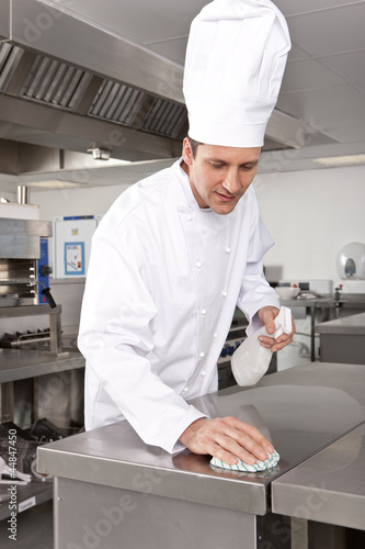 Chef cleaning work surface in commercial kitchen