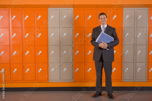 Teacher holding paperwork standing near school lockers