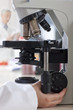 Technician adjusting microscope in laboratory