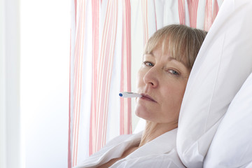 Patient having temperature taken in hospital room