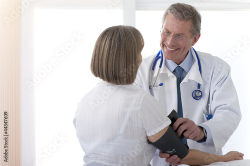Doctor taking patients blood pressure in hospital