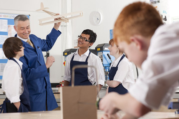 Teacher explaining wooden model airplane to students in vocational classroom