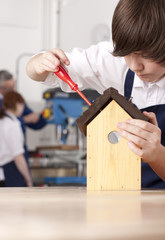 Student attaching roof to birdhouse in woodworking class