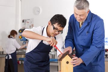 Teacher explaining to student how to attach roof to birdhouse in woodworking class