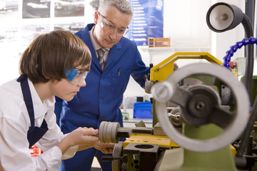 Teacher watching student use lathe in metalwork class