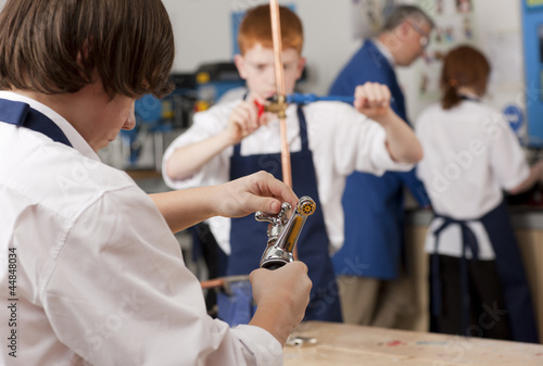 Student looking at plumbing faucet in vocational classroom
