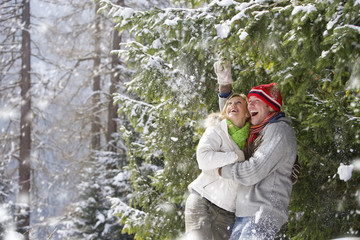 Snow falling on happy couple standing under tree