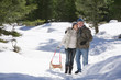 Couple pulling sled in snow