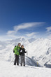 Couple hiking up ski slope on mountain