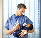 Doctor with baby bottle holding newborn baby boy in hospital