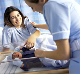 Nurse and smiling mother with newborn baby boy in hospital