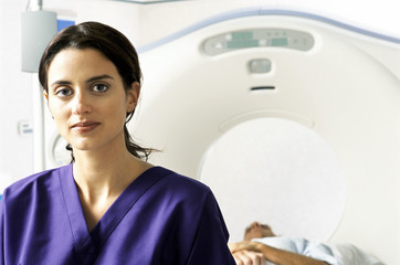 Portrait of nurse with patient in MRI scanner in background