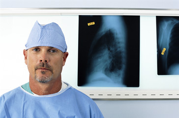 Portrait of serious surgeon in front of x-rays