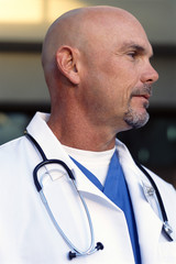 Close up of bald doctor in lab coat with stethoscope