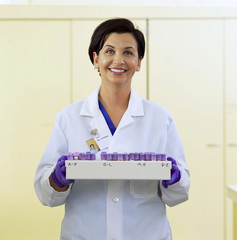 Portrait of smiling pathologist with tray of blood samples