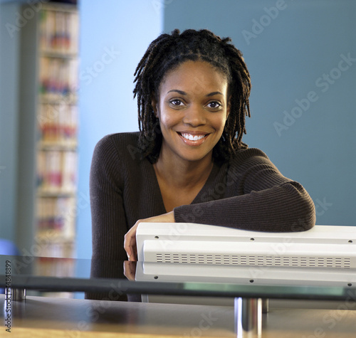 Portrait of smiling nurse leaning on computer at nurses station