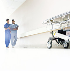 Doctors in scrubs with medical chart talking in hospital corridor