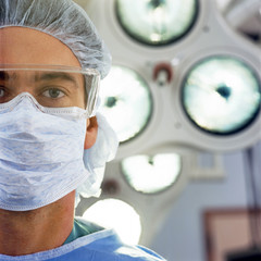 Close up portrait of serious doctor wearing surgical mask and cap in operating room