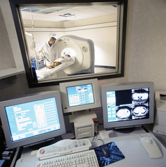 Data and MRI scan on computers with doctor looking over patient in MRI scanner in background