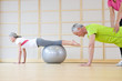 Personal trainer helping senior man balance on fitness ball in exercise class