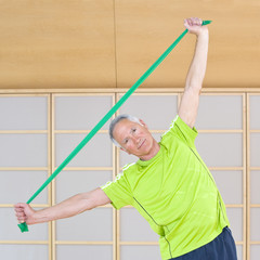 Portrait of senior man exercising with resistance band in gym