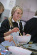 Smiling girl with wooden spoon and bowl cooking in home economics class
