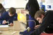 Boy using saw to cut wood in classroom workshop