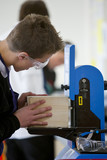 Boy with goggles using woodworking machinery in classroom workshop