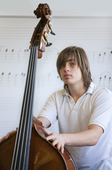 Portrait of boy holding cello in classroom