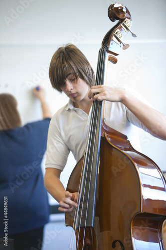Boy practicing cello in classroom