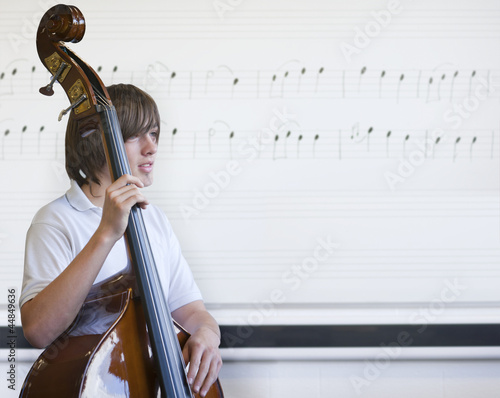 Boy holding cello in classroom with musical notes on whiteboard