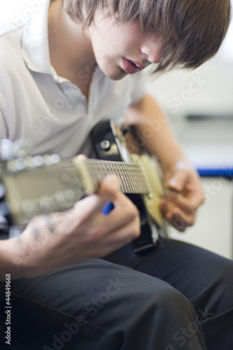 Close up of serious boy playing guitar